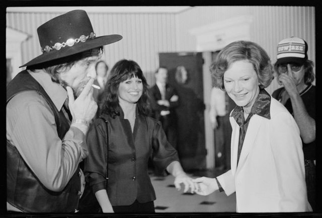[First Lady Rosalynn Carter with Waylon Jennings, smoking a cigarette, and Jesse Colter at a reception preceding a concert to benefit the Carter-Mondale campaign]