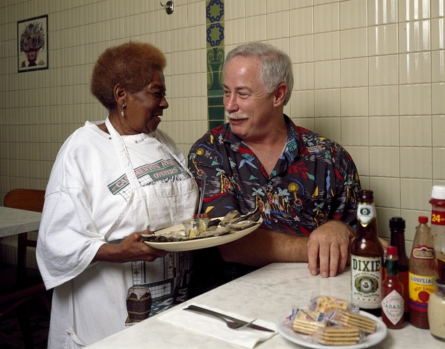New Orleans writer and television personality Ronnie Virgets is served the house specialty, ice-cold oysters on the half shell, by Alma Griffin at Casamento's Seafood Restaurant in Uptown New Orleans, Louisiana