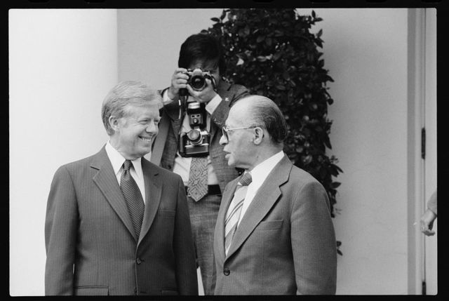 [President Jimmy Carter and Israeli Prime Minister Menachem Begin talk at the White House, Washington, D.C., as a photographer adjusts his camera in the background]