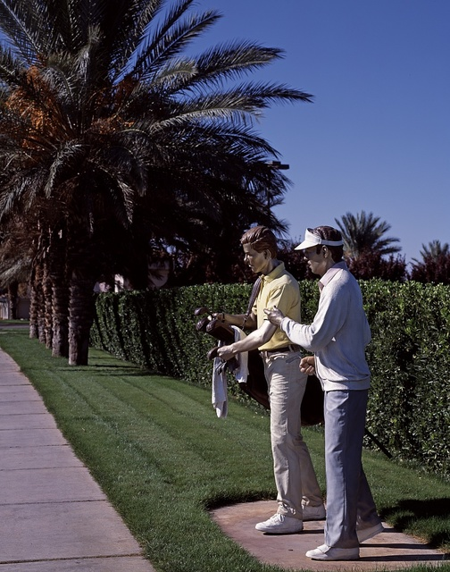 """Two painted bronze """"golfers"""" compare notes outside the Legacy Golf Club in Henderson, Nevada"""
