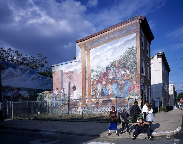 Young boys congregate on the corner in front of a mural in a neighborhood in Philadephia, Pennsylvania