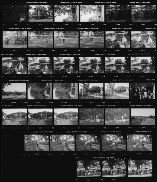 Contact Sheet: 1A-6A Flag-Lowering Ceremony;  7A-9A Willard Phillips Sprays Down Dust in Arena During Supper Break; 10A-17A Dorothy Sara Lee and Dennis Hastings Listen to the Tape of Mr. Edward's Indian Chipmunks;  18A-19A  Pow-Wow Campground from the West;  21A-22A Midway; 23A Booth with Videogames; 24A-28A Pow-Wow Campground from Road on the East; 29A Looking Up Skunk Hollow Road from Pow-Wow to North; 30A-34A Willard Phillips Sprays Down Dust in Arena During Supper Break; 35A-37A Martie Morris and Family Eat Dinner Along the South Side of the Little Arena