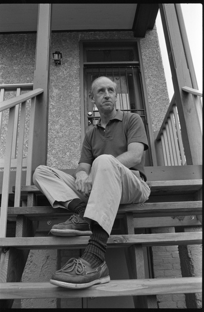 [Builder and property manager Joel Truitt, full-length portrait, seated on steps of a house, facing front, Capitol Hill, Washington, D.C.]