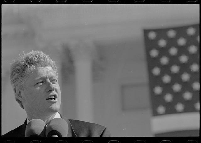 [President Bill Clinton, head-and-shoulders portrait, speaking into a microphone in front of the U.S. Capitol during the ceremony for the returning of the Statute of Freedom to the top of the U.S. Capitol]