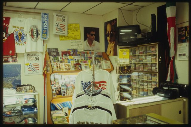 A view into the southeast corner of Sanremo, showing t-shirts, magazine and cassette music racks, posters, etc.  The shop is filled with items from Italy, all, Ralph says, of high quality.