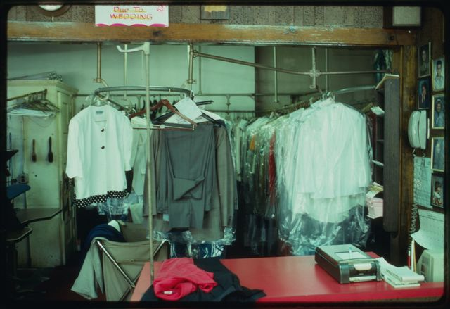 A view over the counter toward racks of dry cleaning and tailoring to be picked up by customers.