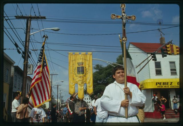 Altar boy with cross and men with banners at the head of the procession.