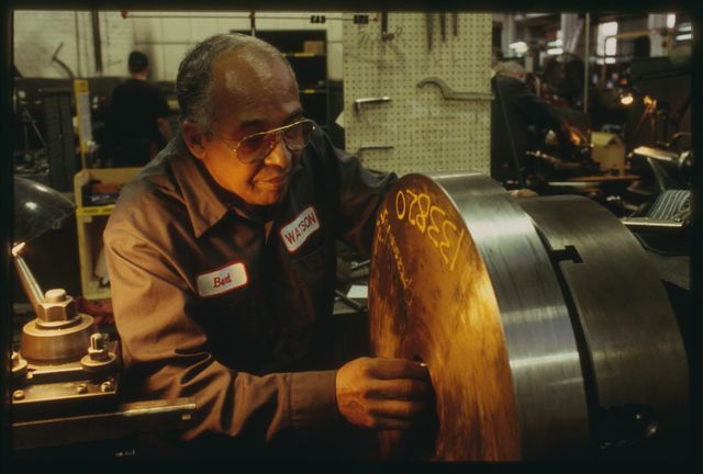 Bert Reales adjusts the cutting tool on the traveler to acquire the proper depth and angle of cut on the flywheel in his lathe.