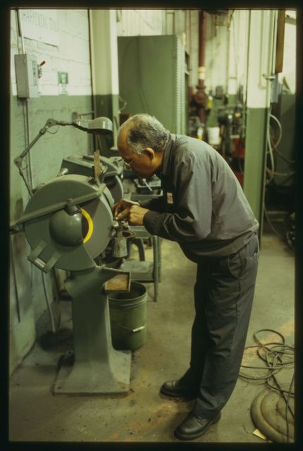 Bert Reales sharpening a cutting tool prior to using it in his lathe.  In larger shops tool cutters were a separate specialty, but at Watson, machinists cut their own tools.