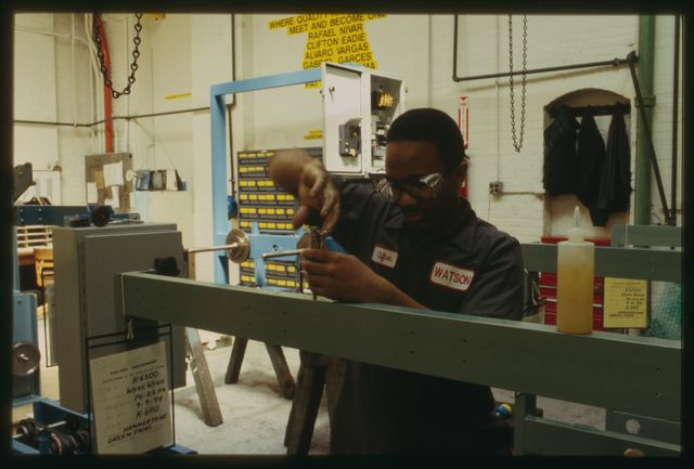 Clifton Eadie tapping holes for screws in a horizontal pay-off machine.