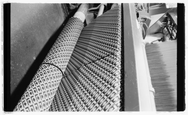 Close-up of fabric being woven on loom.