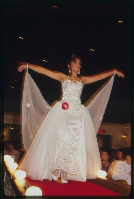 Contestant, in evening gown, walks down runway.