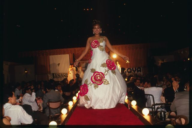 Contestant wearing evening gown walks down the runway.