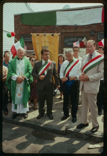 Dignitaries standing in front of the Montescaglioso Club; the tall man in the tan suit is Congressman Herbert Klein, the man in the white shirt is Paterson mayor William Pascrell.
