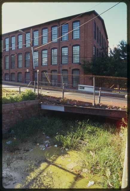 Dry canal, full of weeds and garbage, that is part of the raceway system that formerly supplied hydraulic power to mills; mill building in the background.