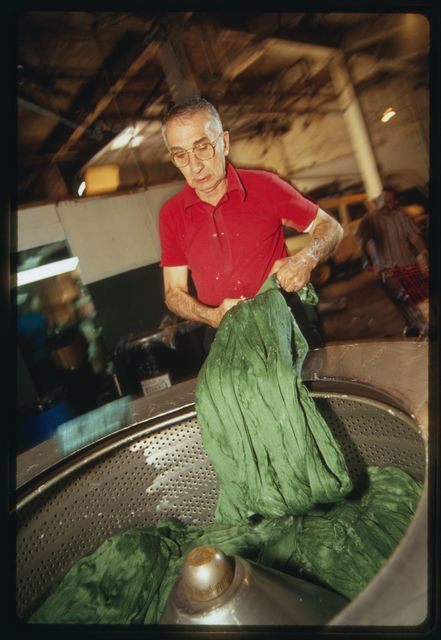Dye house machine operator Martino Cardone putting dyed silk into a spinning machine used to remove water.