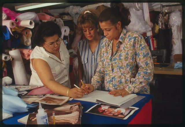 Elsa, Aurora and Milagros work with Brenda to come up with design for her dress; they are using photos (including some taken at Dominican pageant by Martha Cooper) and sketches; an unidentified girl is also present.