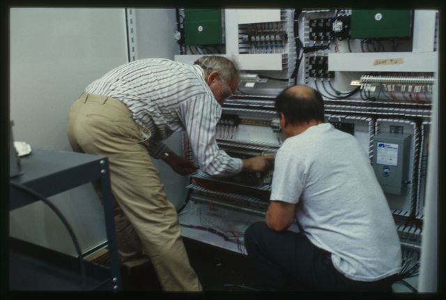Engineer Ernest Milov and electrician Bob Dale check circuits on the service panel of the rotary take-up machine.