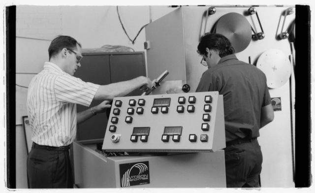 Engineer (white shirt) and machinist work on machine used for fiber-optics applications.