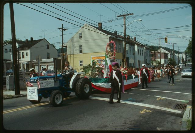 Float carries statue through the streets; members of Knights of Columbus walk beside the float.