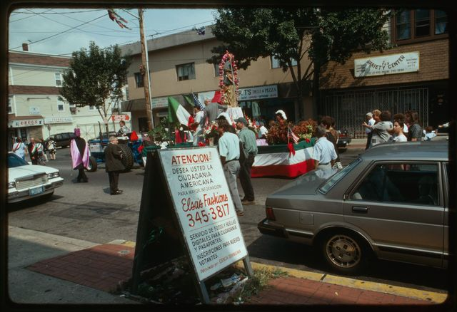Float carrying saint down 21st Avenue; sign in front of Elsa Fashions; fieldworkers Bob McCarl and Tom Carroll (wearing cap) are to the right of the sign.