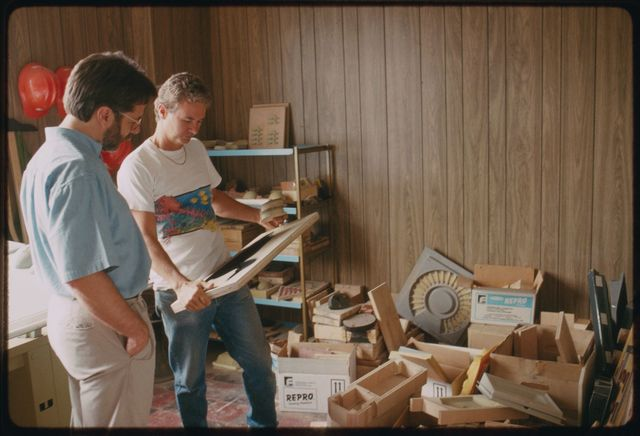 Folklorist David Taylor looking over pattern books and materials at Technocraft, a pattern-making shop in  Bloomfield, New Jersey.  He is accompanied by Sherman  McGovern, one of the patternmakers in the shop.