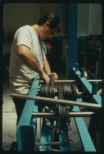 Gabriel Garces installs drive belts in a horizontal pay-off machine.