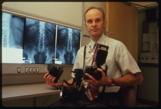 Hospital photographer Richard Green poses for photo with his cameras.