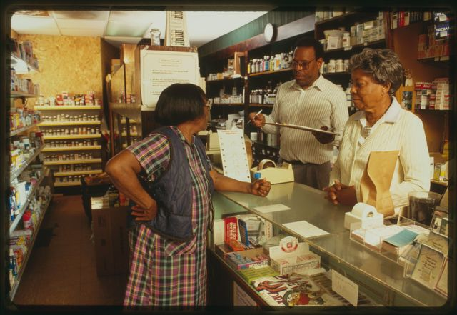 Howard Fulcher and his mother, Ida Fulcher, behind the counter of their pharmacy; customer Eula Mae McCall is visible in the frame.