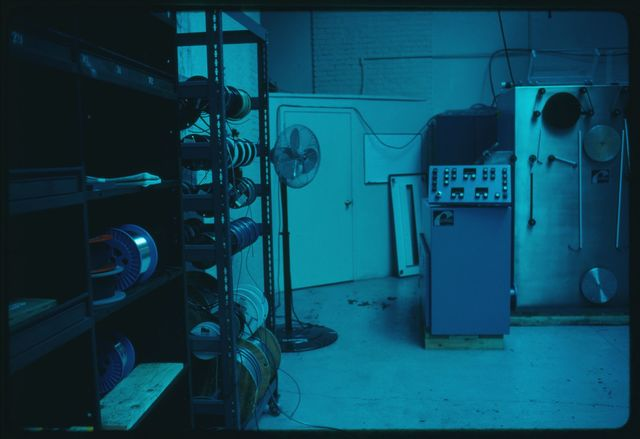 Interior of fiber optics room at Watson with fiber optic proof tester; this machine tests the tensile strength of fiber optic cable while it winds it on to spools.