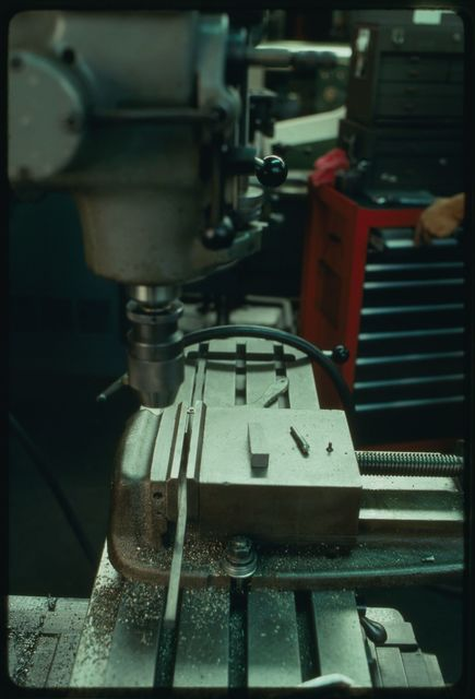 Joe Kachler drilling holes in small shafts using the drill press.