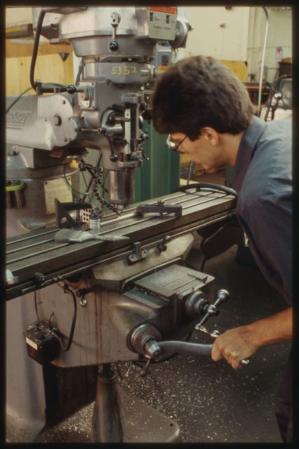 Joe Kachler using a jig to drill holes in a small shaft while it is mounted on the drill press.