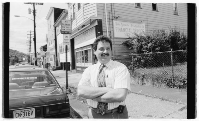 John Granata, proprietor of Granata Financial Service, poses on 21st Avenue; sign for his business in visible behind him.