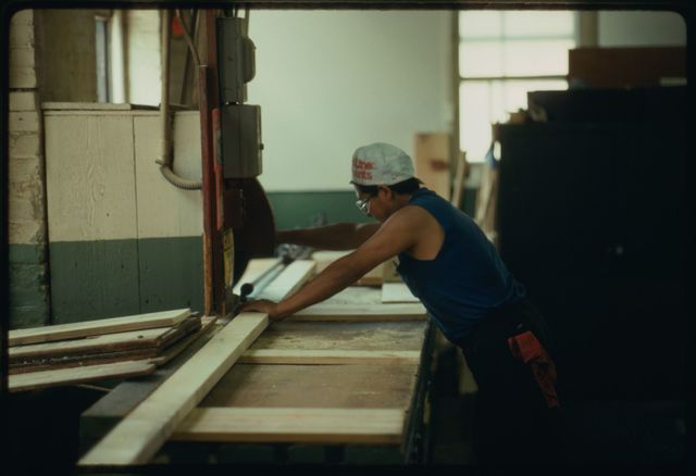 Jose Abanto cutting lumber to build a crate in the woodworking shop above the machine shop floor at Watson.
