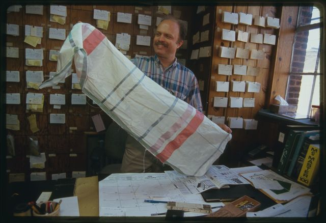 Joseph Teshon, Inc. plant manager examines fabric sample in his office.