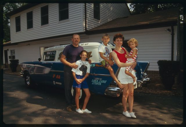 Larry, wife Bonnie, and children Lara, Luke, and Tonya pose beside car.