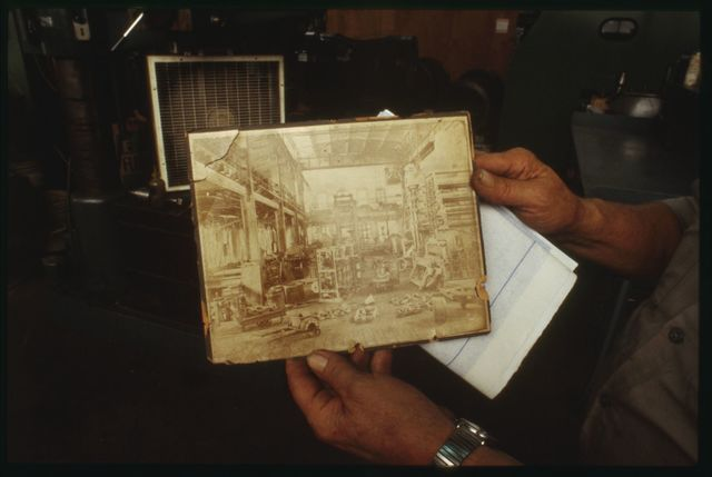 Lead assemblyman Richie Takach holding photograph of Watson Machine Shop circa 1890's. The photograph is taken from almost the spot where Richie currently is standing.