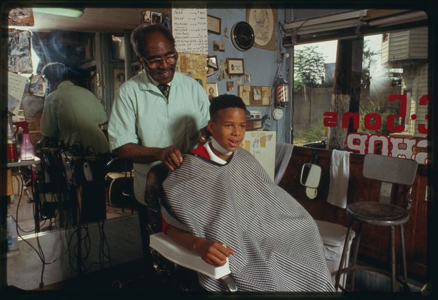 """Louis McDowell cuts Michael Young's hair; the haircut is called a """"high-top fade""""; today is Young's 14th birthday."""