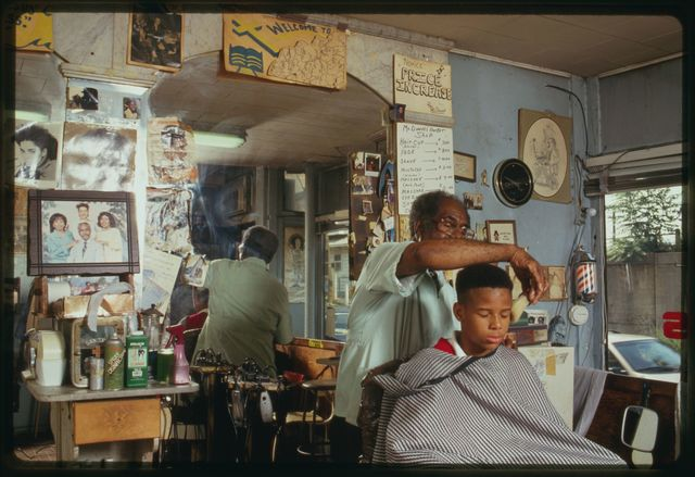 """Louis McDowell gives Michael Young a haircut, the cut is called a """"high-top fade""""."""