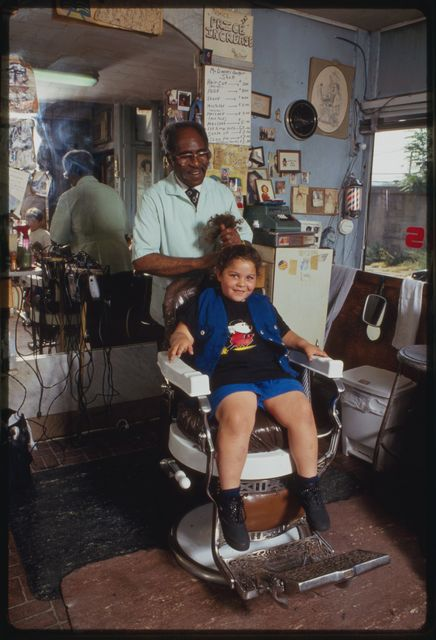 Louis McDowell gives neighborhood girl a haircut as her mother looks on.