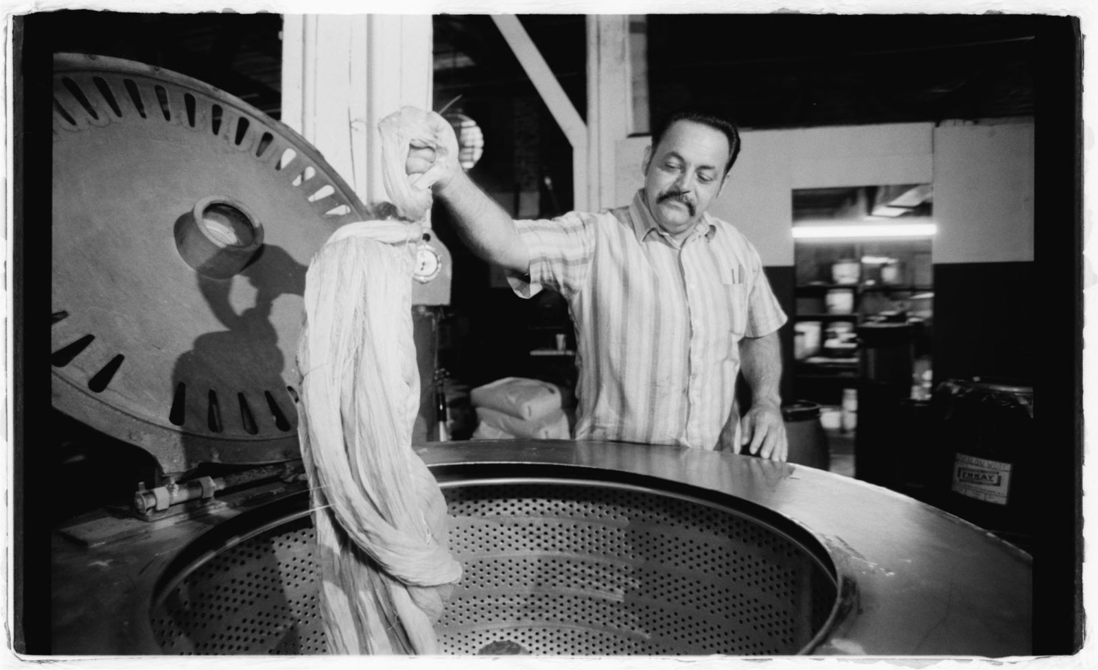 Machine operator Nelson Beniquez washing silk in tanks.
