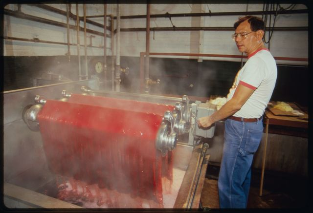 Machine operator Orlando Lee at dyeing tank with silk he is dyeing red.