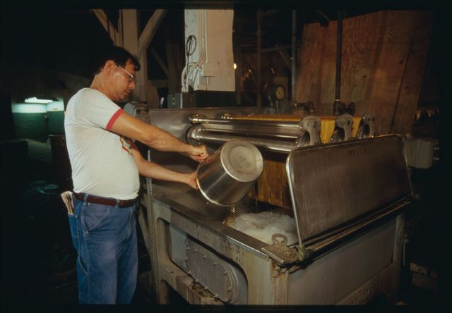 Machine operator Orlando Lee at work at dyeing tank as dye is added.