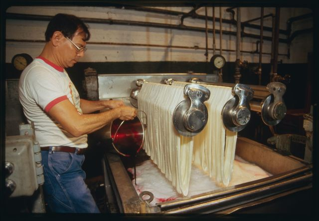 Machine operator Orlando Lee at work at dyeing tank; dye is absorbed by the silk as rollers are rotated.