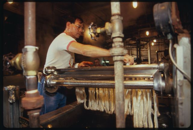 Machine operator Orlando Lee at work at dyeing tank; skeins of undyed silk are placed on rollers.
