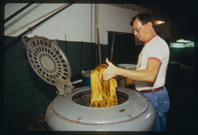 Machine operator Orlando Lee putting silk into spinning machine so it can be spun dry.
