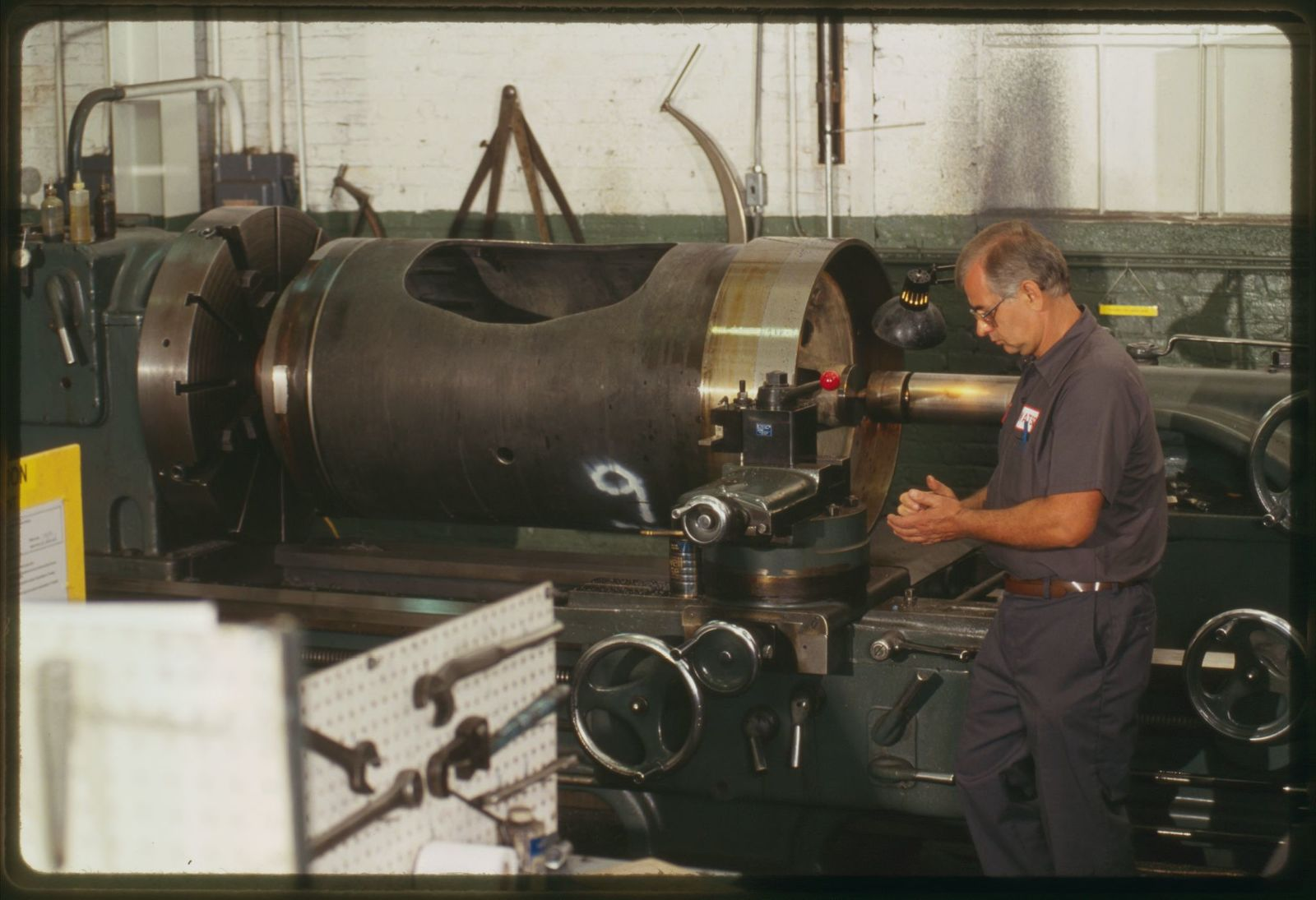 Machinist Jan Sudol works on large cylindrical piece equipment.