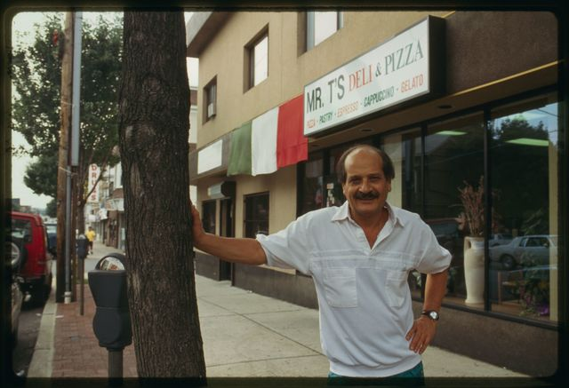 Manager (owner?) of Mr. T's Deli stands outside the shop.