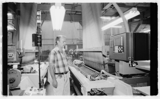 """Mechanic John Clark demonstrates use of computerized device, called a """"controller,"""" that directs operation of a loom."""