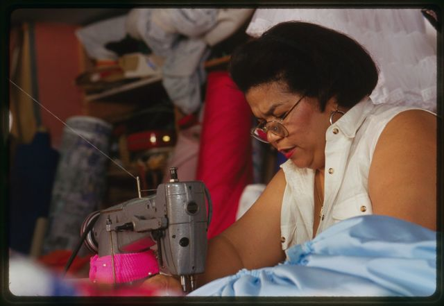 Milagros Cueto works on blue gown.